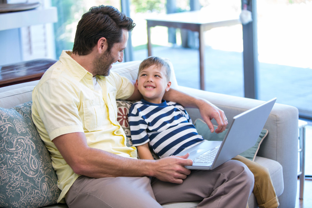 38362927 - father and son using laptop on the couch at home in the living room